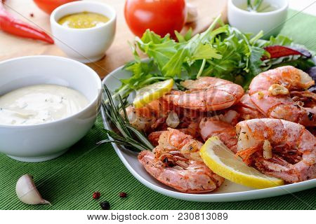 Prawns Shrimps Roasted With Garlic And Rosemary, Served On White Plate With Mizuna Lettuce, Lemon An