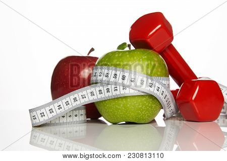 Green And Red Apples With Measuring Tape And Red Weight Dumbbells For Diet Concept On White Backgrou