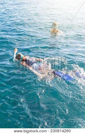 Two Teenagers Enjoying Snorkeling In Turquiose Tropical Sea. Girl Swimming On Sea Surface And Boy Sw