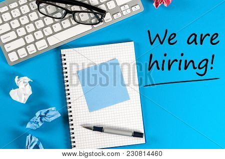 Work Notepad, Keyboard And Glasses On Blue Desk With Text We're Hiring