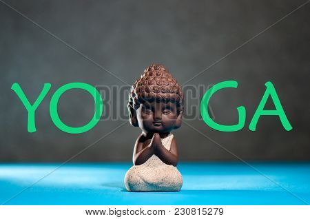 Yoga. Little Buddha With His Hand In Greeting Sign Namaste And Yoga Studio Or Class Concept.