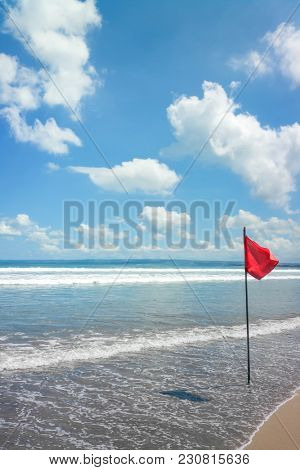 An image of a beach at Bali with a red flag