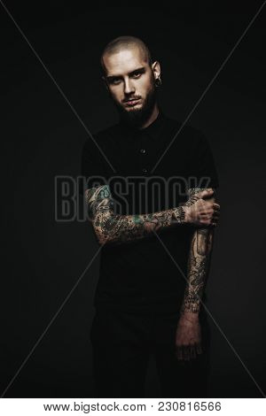 Portrait of a bearded hipster man wearing black t-shirt with piercing in the ears and lips. Studio shot over dark background.