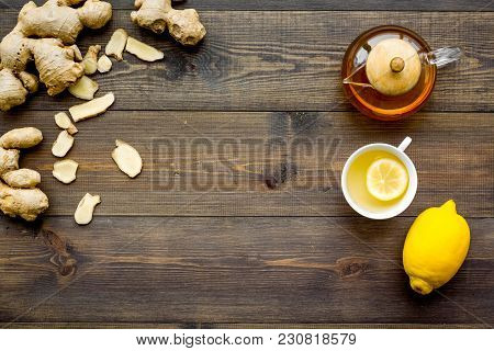 Tea For Cure Colds. Cup, Teapot, Ginger Root And Lemon On Dark Wooden Background Top View.