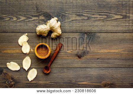 Spice And Condiment. Ground Ginger In Small Bowl Near Ginger Root On Dark Wooden Background Top View