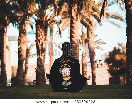 Girl Meditating In Park With Harmonizing Mudra. Young Woman In Black Trendy Jeans Jacket With Ganesh