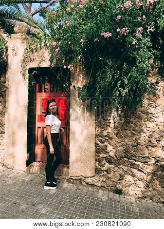 A Young Woman Dressed In Jeans And Sneakers Leans Against A Wall With Red Door In An Ancient City. A