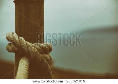 Clove Hitch Knot Tied On A Wooden Post By A Path At The Edge Of A Cliff On The Coast. A Vintage Pict