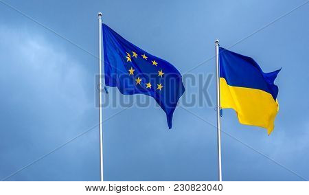 The Flag Of The European Union And Ukraine, Against The Background Of The Sunny Sky. State Symbols,