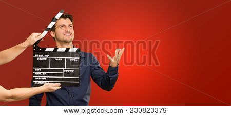 Director Clapping The Clapper Board On Red Background