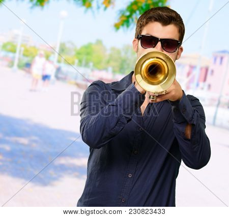 Young Man Wearing Goggles And Blowing Trumpet, Outdoor