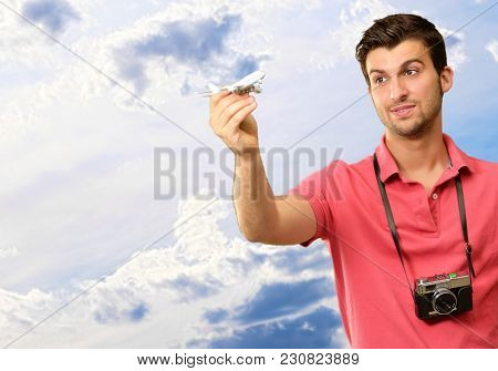 Young Man Holding Airplane And Boarding Pass, Outdoor