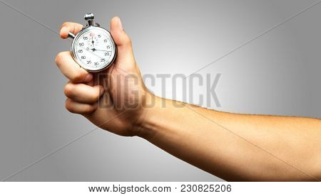 Close Up Of Hand Holding Stopwatch against a grey background