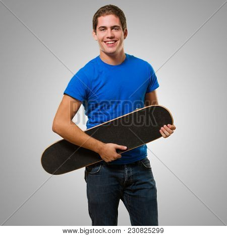 Happy Man Holding Skateboard against a grey background