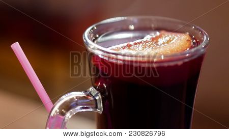 A Cup Of Hot Mulled Wine Served At The Table With Straw