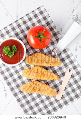 Fried Chicken Dippers On Chopping Board With Sauce And Tomato On Paper Background.top View