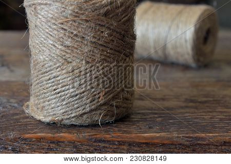 A Close Up Image Of A Spool Of Brown Jute Thread On A Wooden Table.