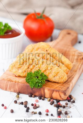 Fried Chicken Dippers On Chopping Board With Sauce And Tomato On Wooden Background