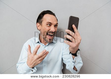 Portrait of a furious mature man dressed in shirt yelling at mobile phone over gray background