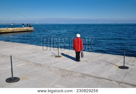 A Woman In A Red Coat Alone On The Beach Expects Her Beloved. The Concept Of A Lifestyle Of A Health