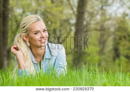 Young blonde woman laying on green grass in spring park