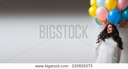 Beautiful young woman with many colorful balloons, copy space for text