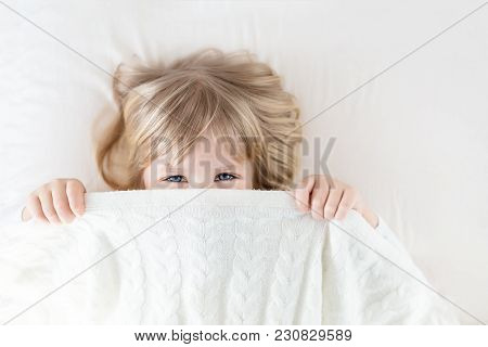 Little Girl Peeking Out Blanket On Bed. Cute Kid Smiling And Hiding Under Knitted Cover. Palyful And
