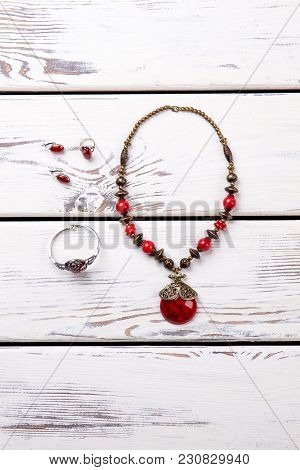 Vertical Photo Of Necklace With Amulet, Bracelet, Earrings. Jewelery Arrangement On The Beige Wooden