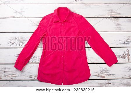 Pink Long-sleeved Shirt, Top View. Red Blouse, Bright Beige Wooden Desks Surface Background.