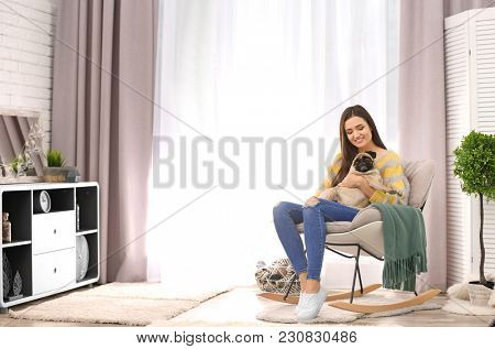 Woman with cute dog at home. Friendship between pet and owner
