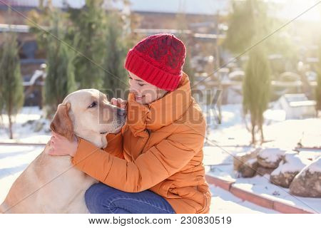 Woman hugging cute dog outdoors on winter day. Friendship between pet and owner