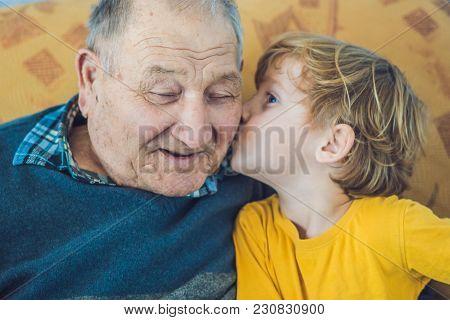 Portrait Of A Happy Boy Kissing Happy Granddad At Home