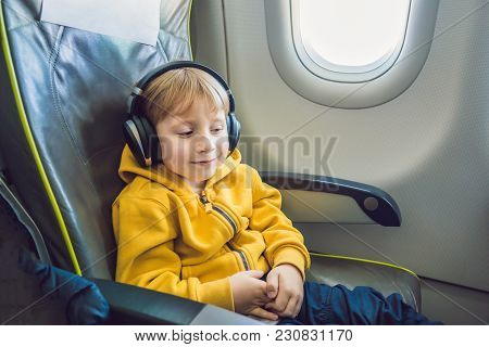 Boy With Headphones Watching And Listening To In Flight Entertainment On Board Airplane.
