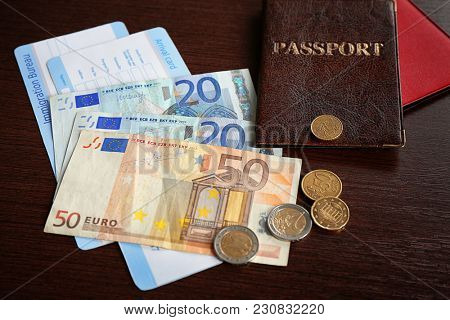 Passports, money and arrival cards on wooden background. Immigration reform