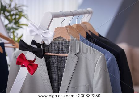 Hangers with suits and bow ties on rack in tailor's workshop