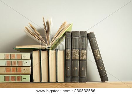 Open Book On Stack Of Books On Wooden Table. Education Concept. Back To School. Copy Space For Text.