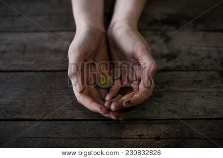 Poor woman with coins on wooden background
