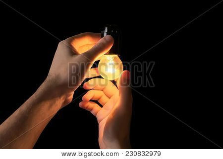 Man with light bulb on black background. Lamp changing