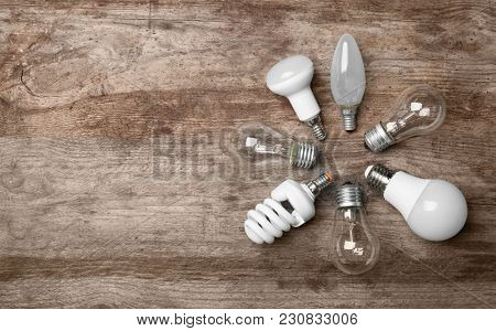 LED, incandescent and fluorescent lamps on wooden background