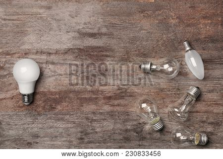 LED and incandescent lamps on wooden background
