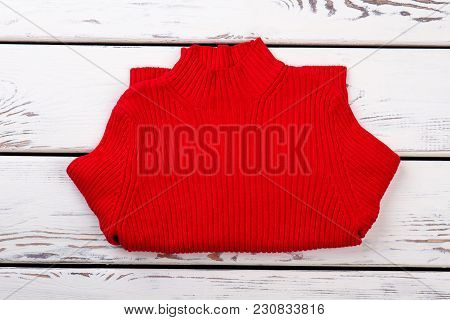 Horizontally Folded Red Sweater. Bended Pullover, Bright Wooden Desk Background.