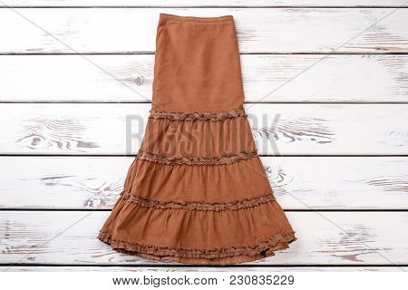 Brown Fashionable Skirt. Full Size Skirt, Top View. White Wooden Desks Surface Background.