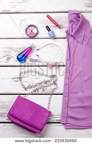 Makeup Cosmetics And Clothes. Purple Shirt And Purse With Chain Handle. Vertical Cropped View.
