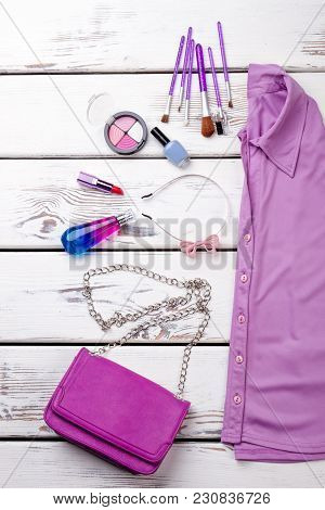 Flat Lay Accessories For Makeup And Violet Shirt. Brushes, Powder, Lacquer And Perfume. White Wooden