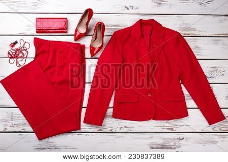 Flat Lay Red Women Suit And Accessories. Jacket, Trousers, Wallet, Shoes, Necklace Beads And Lacquer