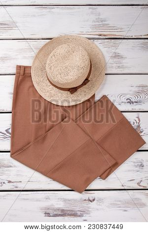 Flat Lay Brown Trousers And Summer Hat. Bright Wooden Desks Surface Background, Vertical View.