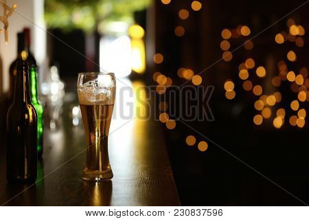 Glass of beer on table against blurred background