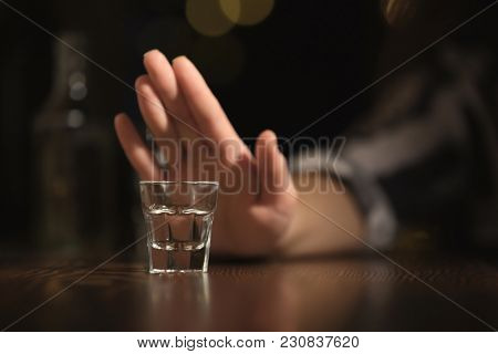 Woman refusing to drink alcohol in bar, closeup