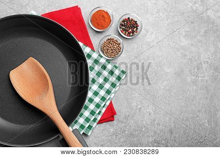 Cooking utensils and spices on gray background, top view