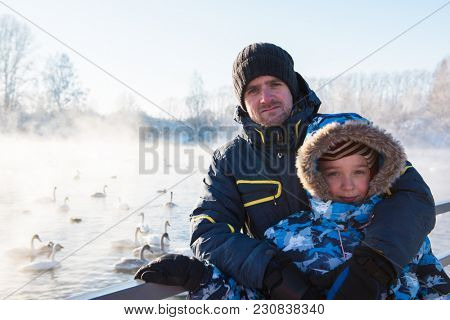 Man with son at winter nonfreezing lake with white whooping swans. The place of wintering of swans, Altay, Siberia, Russia.